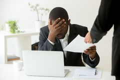 Frustrated upset african american employee receiving dismissal n. Frustrated upset african american office employee receiving dismissal notice at workplace royalty free stock image