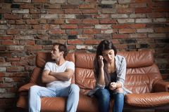 Frustrated upset couple after quarrel sitting on sofa at home. Frustrated upset couple in quarrel not talking after fight, offended stubborn insulted jealous men Royalty Free Stock Photography