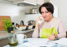 Frustrated woman with banking documents indoors Royalty Free Stock Photos