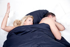 Frustrated woman in bed with her husband Stock Photography