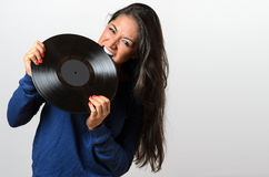 Frustrated woman biting on a vinyl record Royalty Free Stock Photo