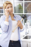 Frustrated Woman Calling Plumber To Fix Blocked Sink At Home Stock Photography