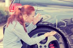 Frustrated woman checking pointing at car scratches dents. Frustrated young woman checking pointing at car scratches and dents outdoors outside Stock Images