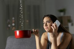 Frustrated woman claiming insurance for water leaks. Sitting on a couch in the living room at home stock photography