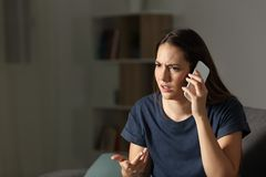 Frustrated woman claiming on the phone in the night. Sitting on a couch at home Stock Photography