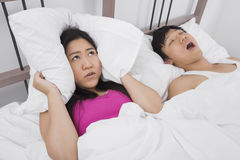 Frustrated woman covering ears with pillow while man snoring in bed Royalty Free Stock Image