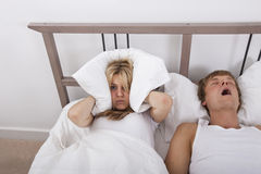 Frustrated woman covering ears with pillow while man snoring in bed Royalty Free Stock Photography