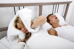 Frustrated woman covering ears with pillow while man snoring in bed Stock Photos