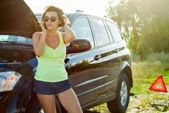 Frustrated woman driver near a broken car. A car on a country ro. Ad, a woman calls asking for help Stock Image