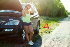 Frustrated woman driver near a broken car. A car on a country ro. Ad, a woman calls asking for help Royalty Free Stock Image
