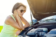 Frustrated woman driver near broken car. Machine on a country road. The woman has stress Royalty Free Stock Image
