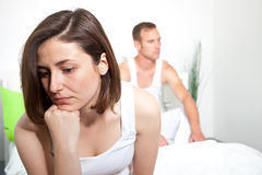Frustrated woman experiencing intimacy problems. Frustrated sad women sitting on the edge of the bed with the back to his partner, experiencing communication and Stock Photo