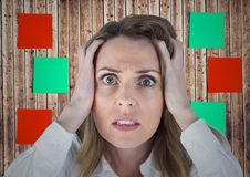 Frustrated woman with hands on her face against sticky note on wooden background Stock Images