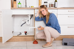 Frustrated Woman Having Kitchen Sink Problem. Young Frustrated Woman Having Sink Problem Trying To Fix Sewer Drainage In Kitchen Royalty Free Stock Photo
