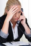 Frustrated woman holding. A frustrated woman telephoned the office. stress and strain in the workplace Stock Photos