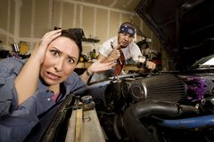Frustrated woman with incompetent mechanic in back Royalty Free Stock Images