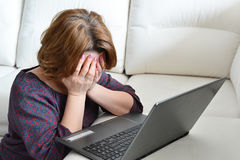 Frustrated woman at a laptop at home. Frustrated woman at a laptop at a home royalty free stock images