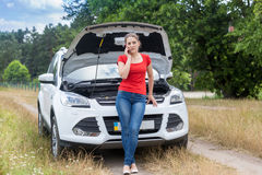 Frustrated woman leaning on broken car in field and calling for Royalty Free Stock Photos