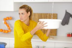 Frustrated woman looking at home water leaks stock photos
