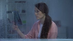 Frustrated woman looking on lungs x-ray on rainy day, incurable disease, cancer. Stock footage stock footage