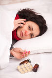 Frustrated woman lying in bed with pills royalty free stock photography