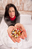 Frustrated woman lying in bed with pills Stock Image