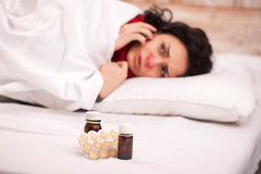Frustrated woman lying in bed with pills. She is unwell. Young sick woman lying in bed with red nose in thick scarf and talking over the telephone having Stock Photos
