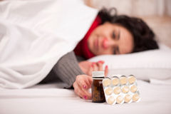 Frustrated woman lying in bed with pills Royalty Free Stock Photos