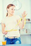 Frustrated woman measuring waist Stock Images