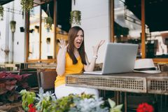 Frustrated woman in outdoors street coffee shop cafe sitting at table with modern laptop pc computer, spreading hands royalty free stock images