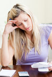 Frustrated woman paying her bills Royalty Free Stock Photos