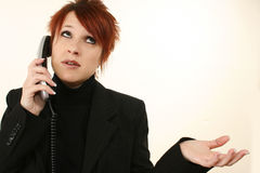 Frustrated Woman On Phone. Attractive 30 year old frustrated woman on landline telephone in suit Stock Images