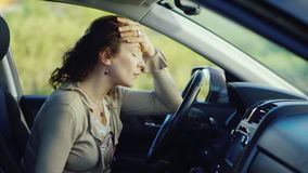 A frustrated woman with a phone sits in the car. Ready to cry, very sad. Concept - depression, women`s problems. HD video stock footage