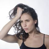 Frustrated woman pulling hair. Portrait of a frustrated young woman pulling her hair Royalty Free Stock Photos