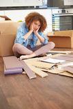 Frustrated Woman Putting Together Self Assembly Furniture. With Head In Hands Looking Annoyed royalty free stock photography