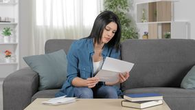 Frustrated woman reading a letter at home stock video footage