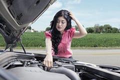 Frustrated woman repairing broken car Stock Photography
