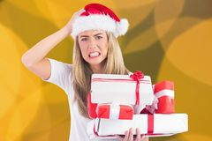 Frustrated woman in santa hat holding stack of gifts Royalty Free Stock Image