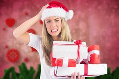 Frustrated woman in santa hat holding stack of gifts Stock Photos