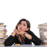 Frustrated woman sits in stacks of books looking up Royalty Free Stock Photo