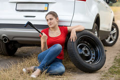 Frustrated woman sitting next to broken car and trying to change Stock Images