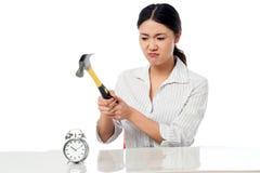 Frustrated woman smashing an alarm clock Stock Photos
