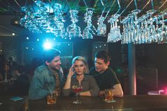 Frustrated woman talking with glad males. They are so boring. Disappointed female with pain in head hearing communication of two cheerful men. Rest in club Stock Images