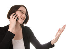 Frustrated woman talking on a mobile telephone. A frustrated woman talks on a mobile or cell phone and waves her hand in anger Stock Image