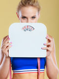 Frustrated woman unhappy with weight gain. Frustrated sad blonde girl covering her face with scales. Weight gain, time for slimming weightloss, diet Royalty Free Stock Images