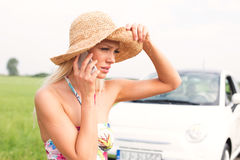 Frustrated woman using cell phone by broken down car Stock Photo