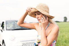 Frustrated woman using cell phone by broken down car Royalty Free Stock Image