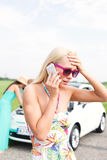 Frustrated woman using cell phone while friend examining broken down car at countryside Royalty Free Stock Image