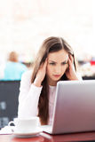 Frustrated woman working on her laptop. In cafe Royalty Free Stock Photos