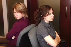 Frustrated at work. Two frustrated businesswomen are angry at each other royalty free stock photography